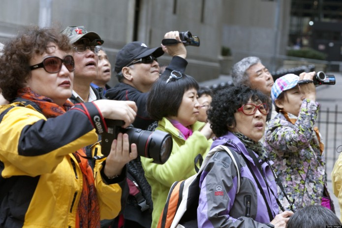 NEW YORK, NY - APRIL 11: Chinese tourists take photos on Wall Street near the New York Stock Exchange, NYSE, on April 11, 2013 in New York, New York. The growing affluence and openness in China allows the Chinese to travel. New York is a popular destination for Americans and foreigners. (Photo by Melanie Stetson Freeman/The Christian Science Monitor via Getty Images)